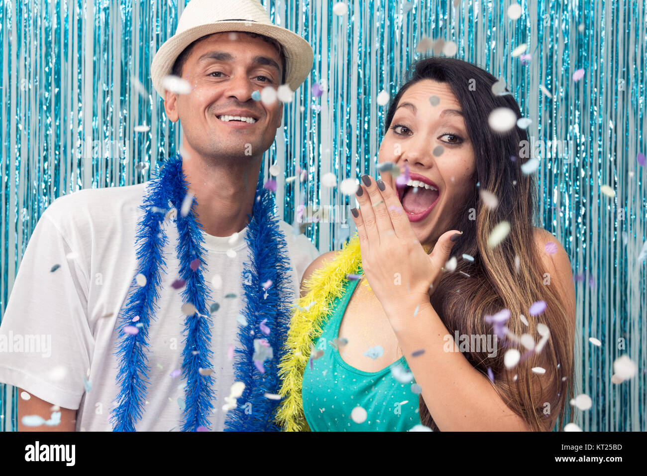 Brazilian couple is at a Carnaval party. He is black and she has Asian ancestry. Colors: Blue, Green and Yellow. - Stock Image