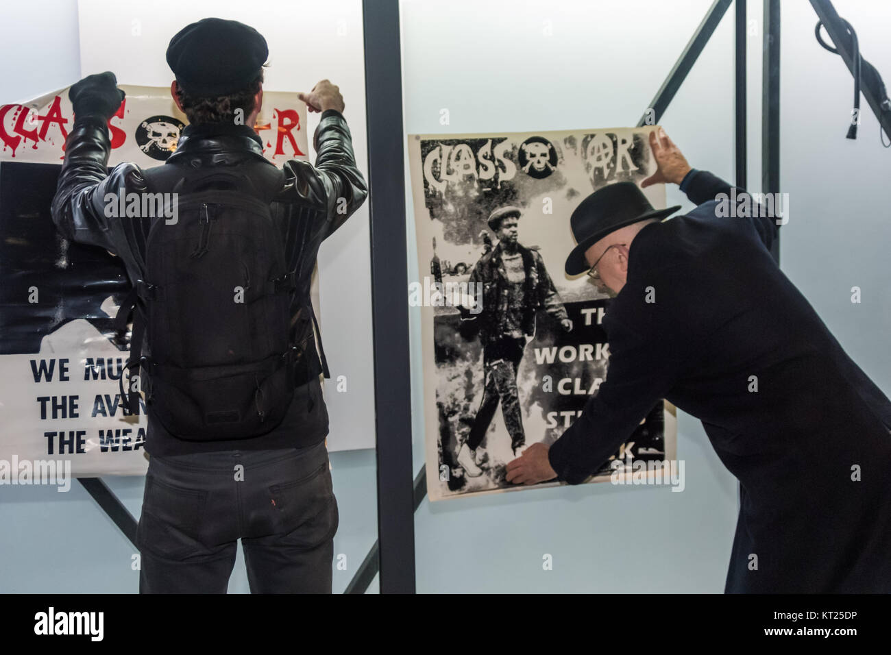 Ian Bone and Simon Elmer put up Class War's posters with Blutak on the front of a currently unused display area - Stock Image