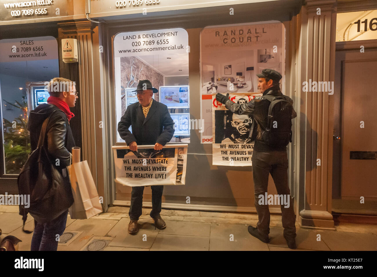 People passing by stopped to talk with Ian Bone and Simon Elmer as they displayed the Class War posters on the windows - Stock Image