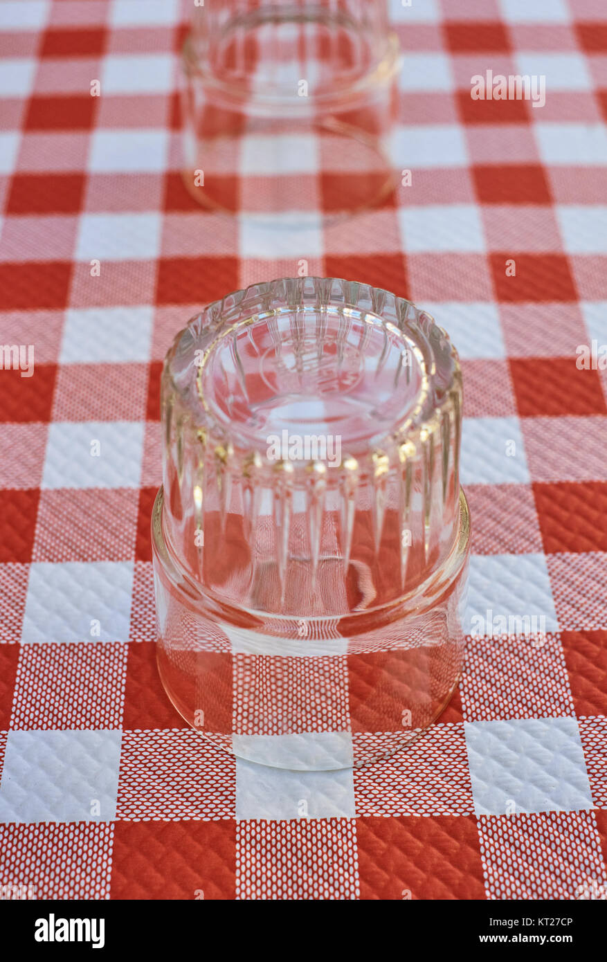 A classic red Gingham check table cloth with glass - Stock Image