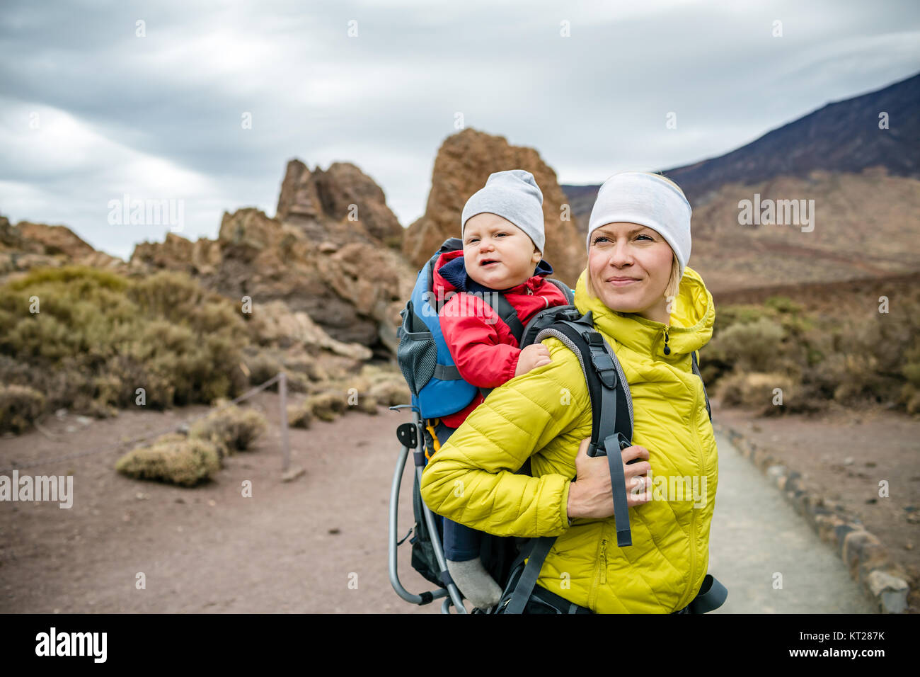 Super mom with baby boy travelling in backpack. Mother on hiking adventure with child, family trip in mountains. - Stock Image