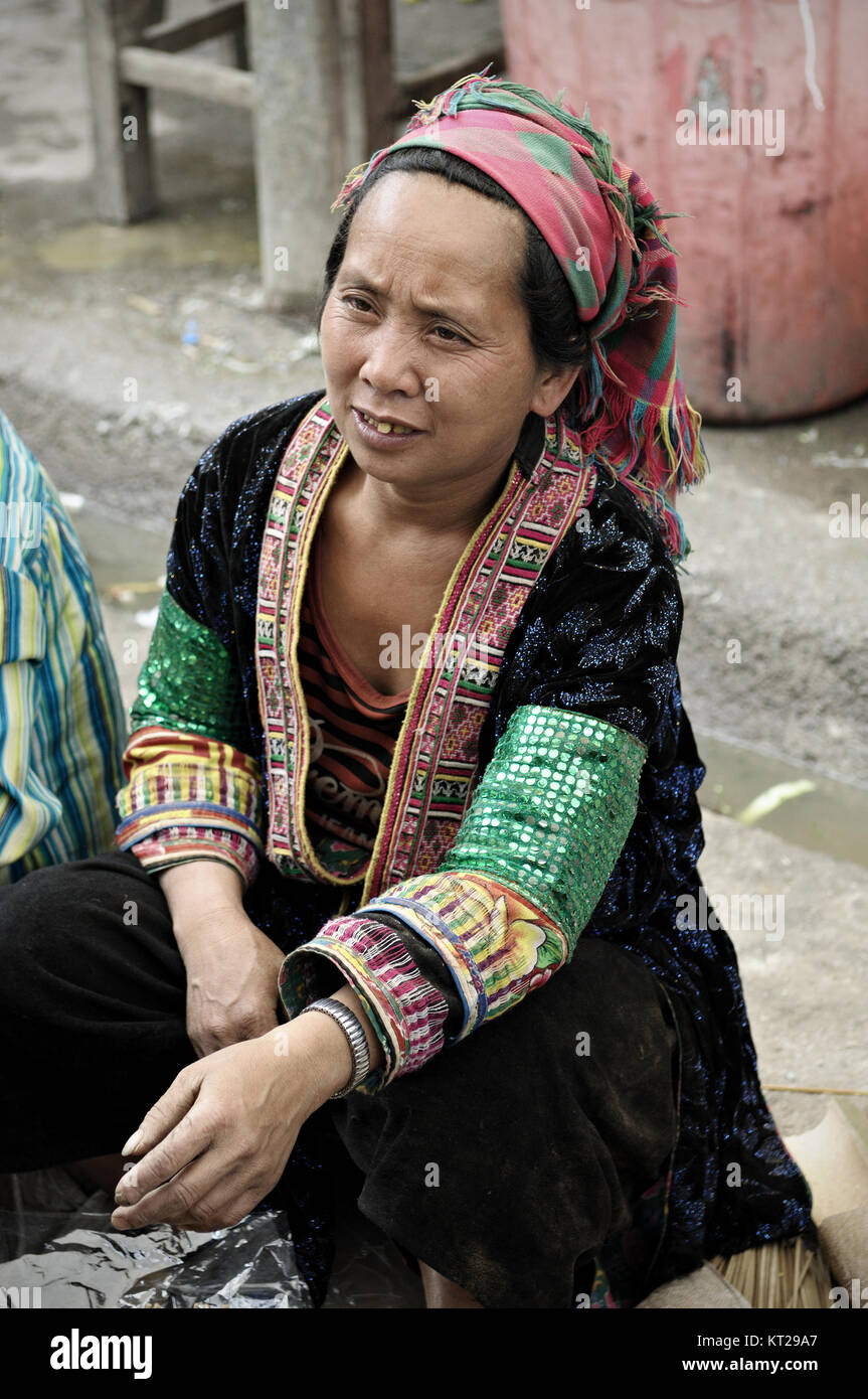 Tribeswoman with traditional dress sitting at Meo Vac market, Ha Giang province, north Vietnam - Stock Image