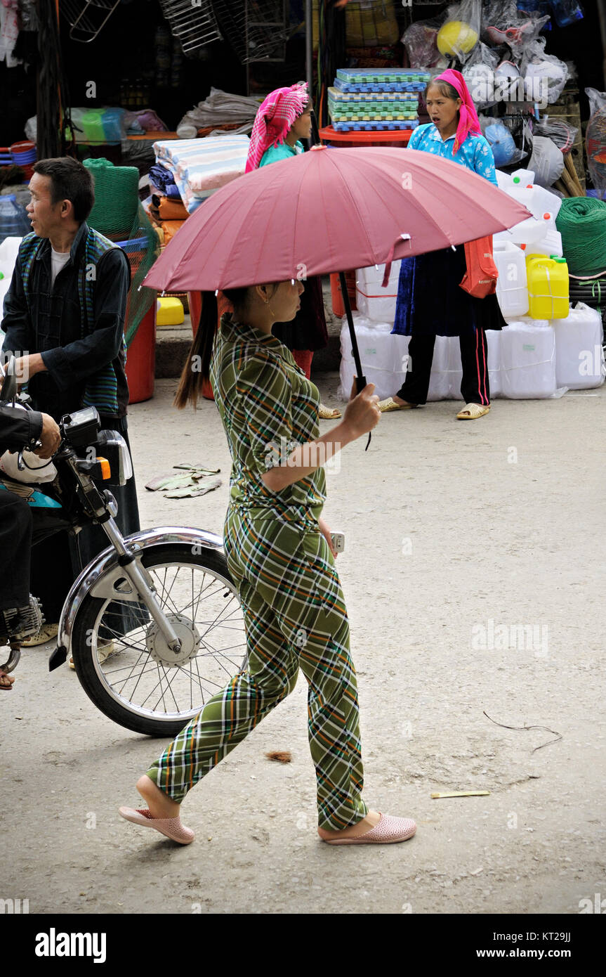 Young woman with an umbrella at the Meo Vac market, Ha Giang province, north Vietnam Stock Photo