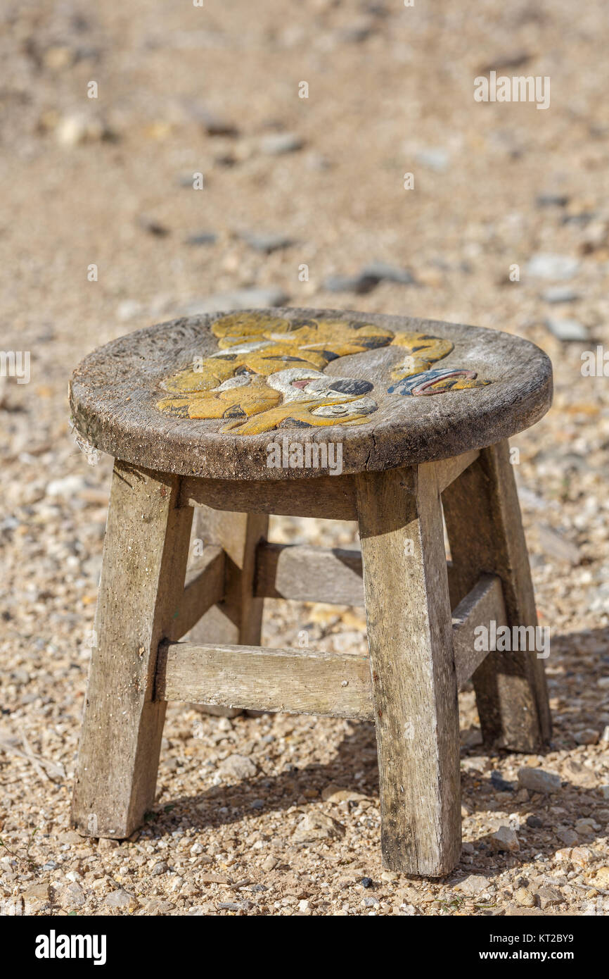 Old, antique, handmade little chair with a round seat stands on the street - Stock Image