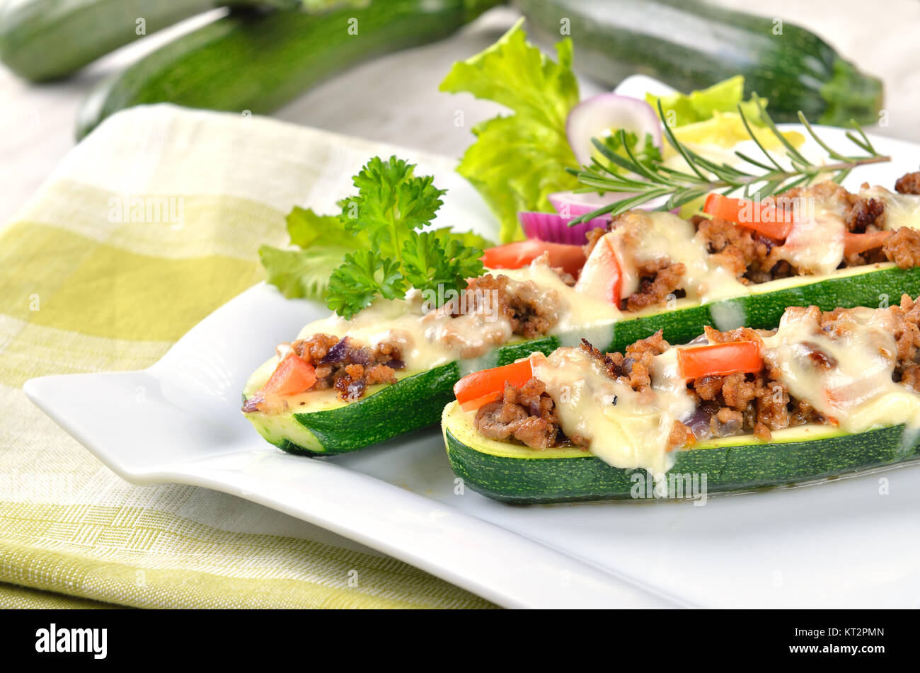 Zucchini halves stuffed with minced meat and gratinated with mozzarella - Stock Image