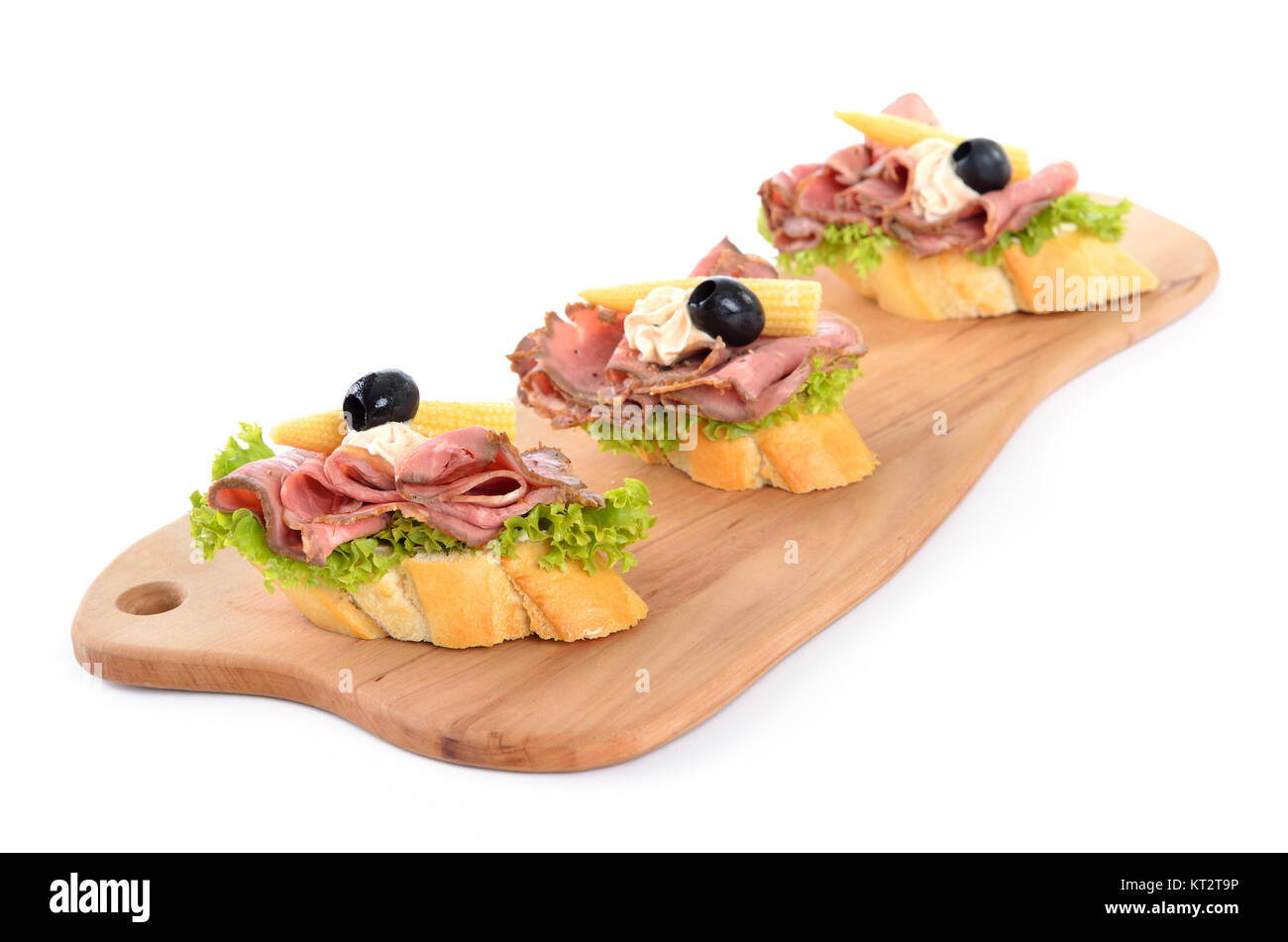 Baguette with roast beef, small corn cobs, cream cheese and black olives on an wooden cutting board - Stock Image