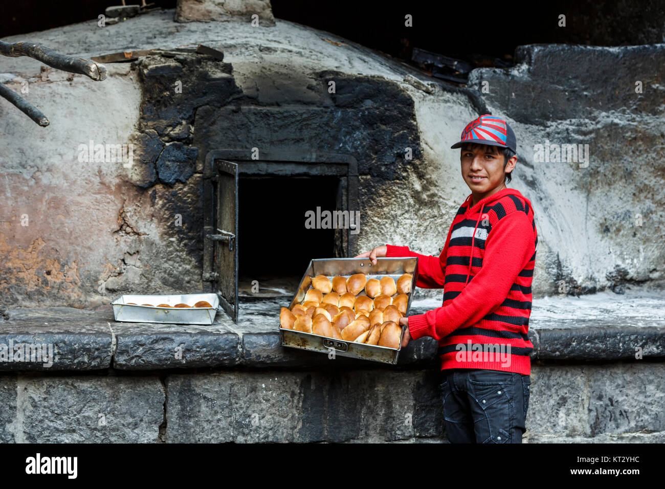 Male server with empanadas in front of historic Horno Colonial San Francisco (San Francisco Colonial Oven), Village - Stock Image