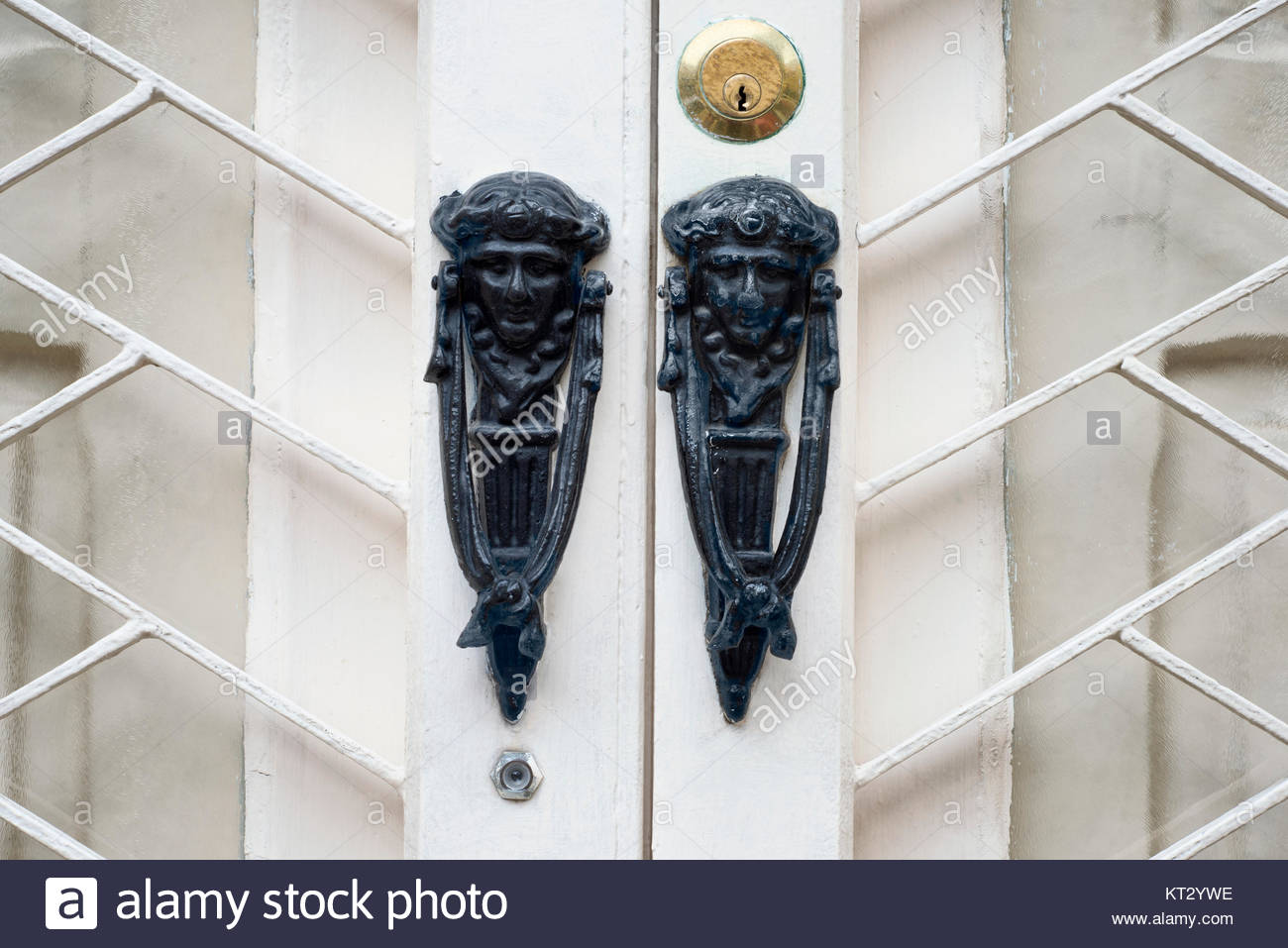 Antique knocker on a vintage wooden white door. Architecture in St. Julian, Malta. - Stock Image