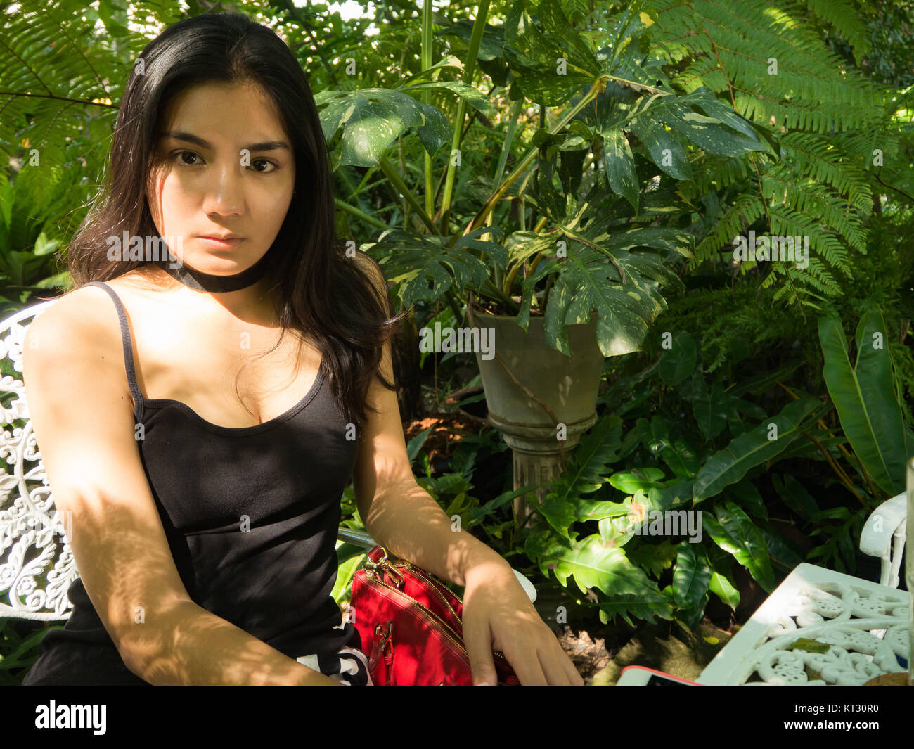 Asian woman sitting on the wooden chair in the garden - Stock Image