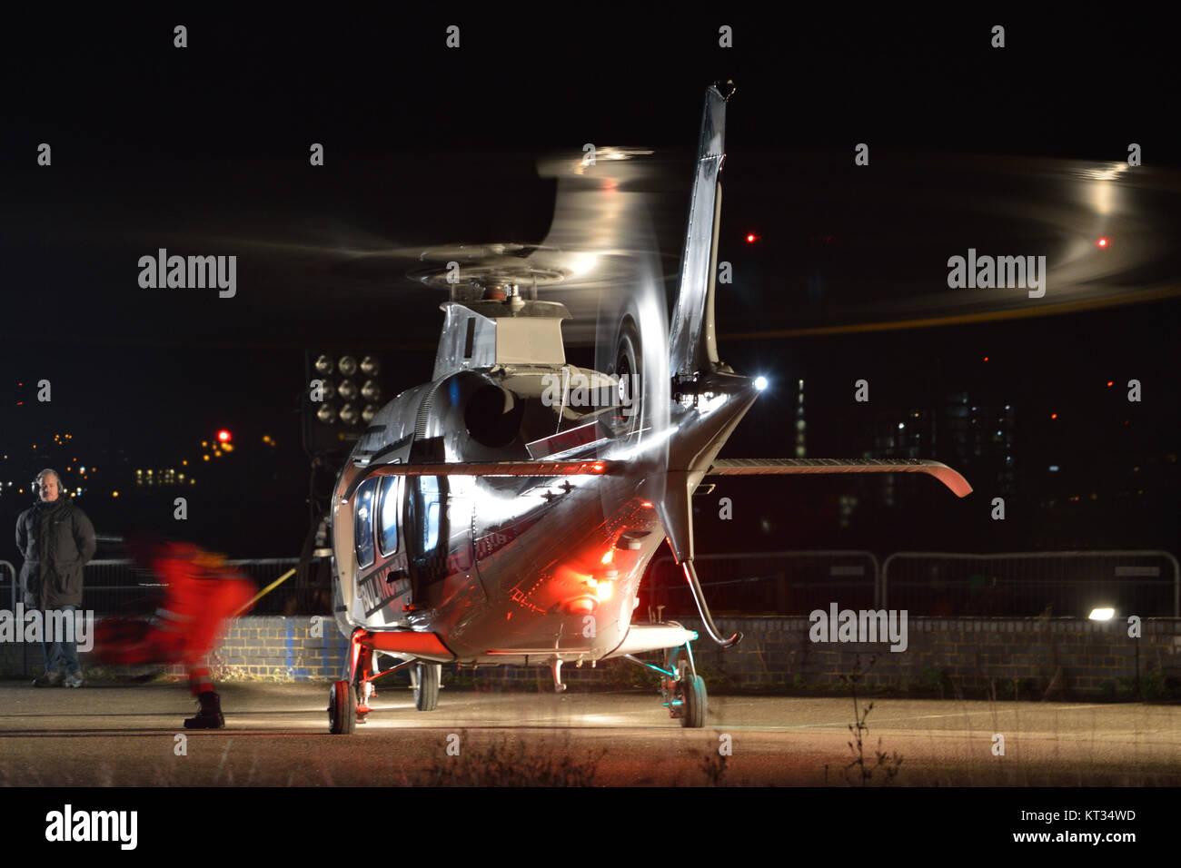 Helicopter being used as a prop on a film set during a night time film shoot taking place on Albert Island in London's - Stock Image
