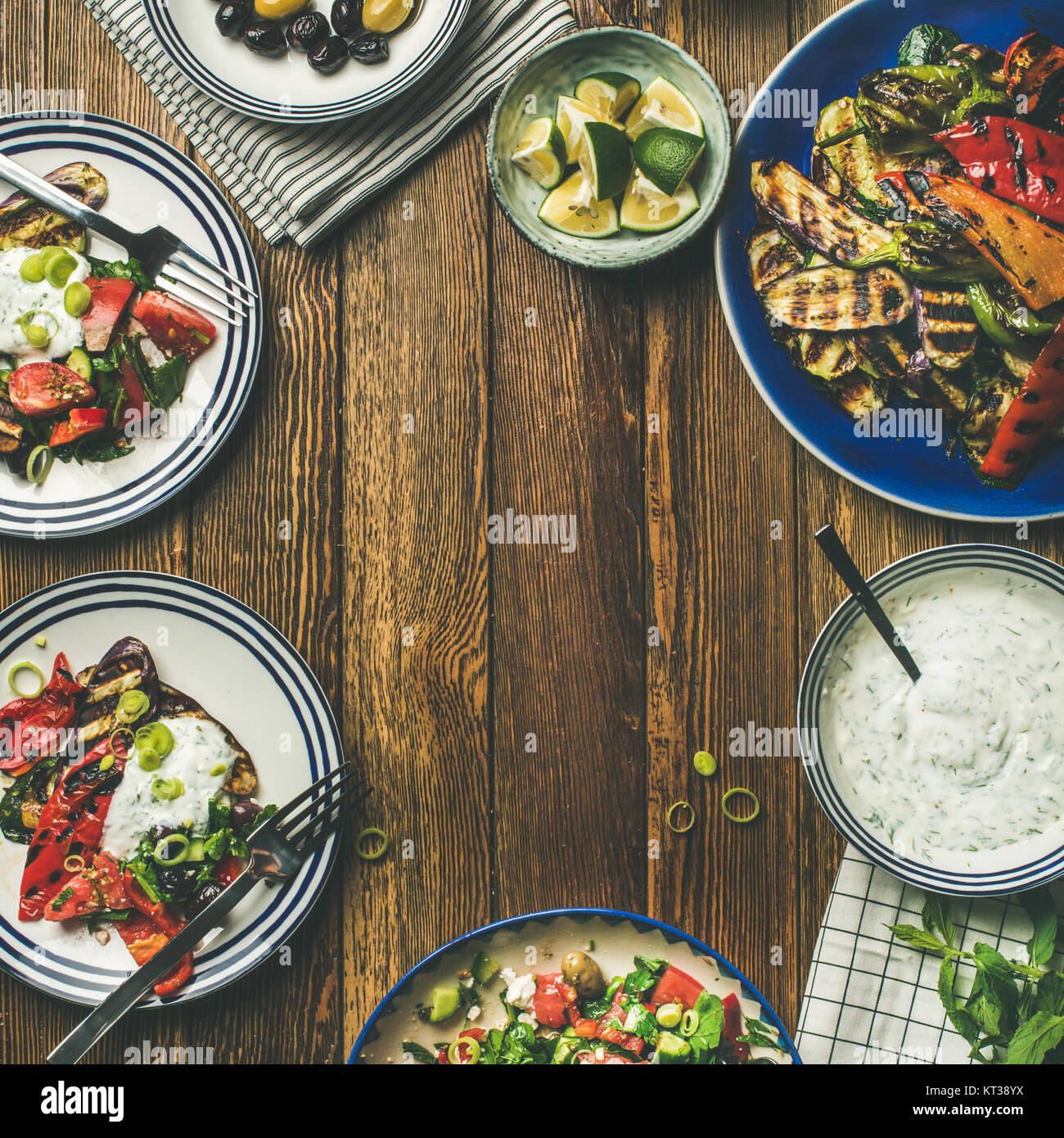 Flat-lay of healthy dinner table setting. Fresh salad, grilled vegetables with yogurt and dill sauce, pickled olives, - Stock Image