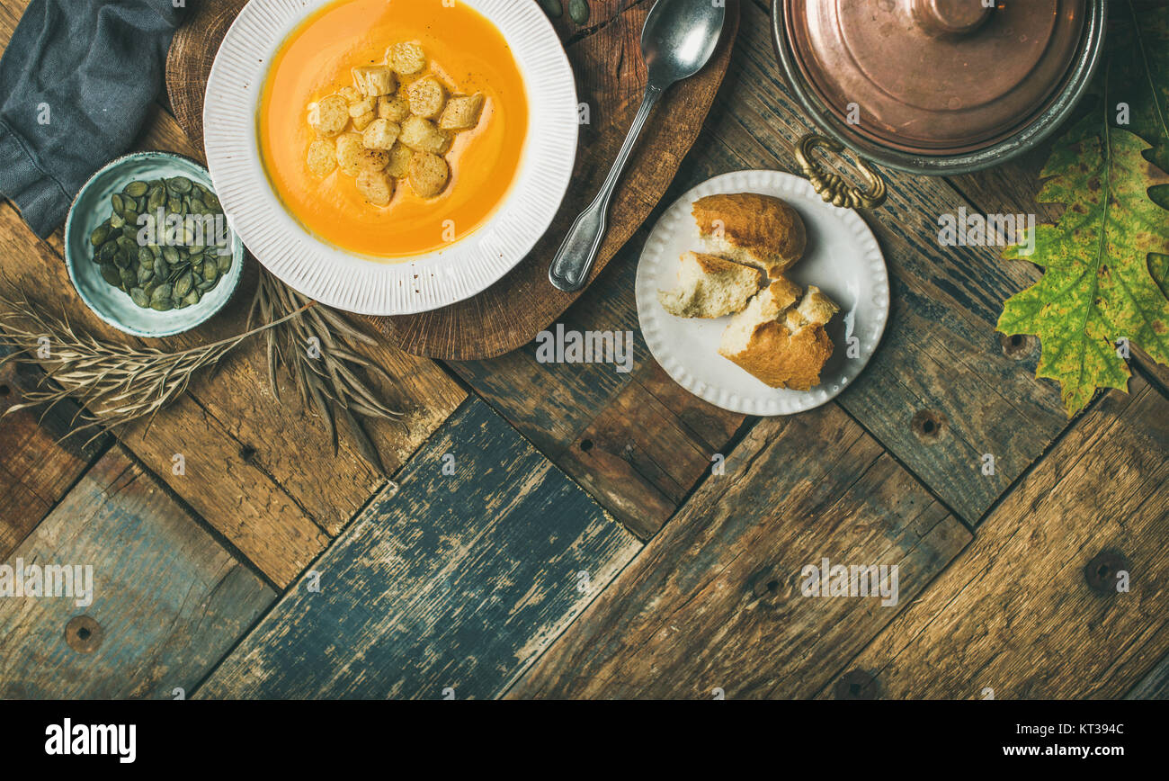 Fall warming pumpkin cream soup with croutons and seeds on board over rustic wooden background, copy space, flat - Stock Image