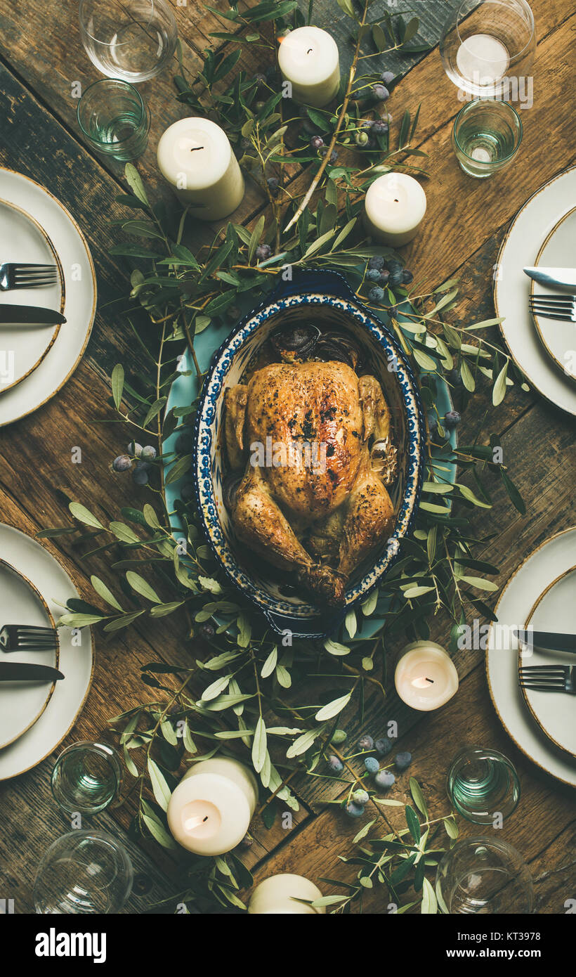 Flat-lay of whole roasted chicken in tray for Christmas eve celebration, plates, glasses and candles over rustic - Stock Image