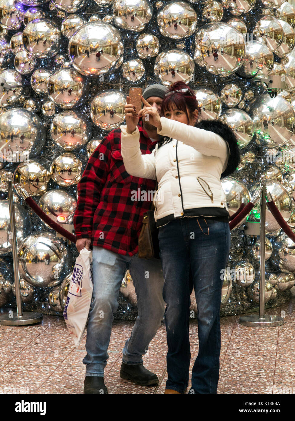 Man and woman taking a selfie in front of the Christmas tree in the Grosvenor shopping centre Chester Cheshire England - Stock Image
