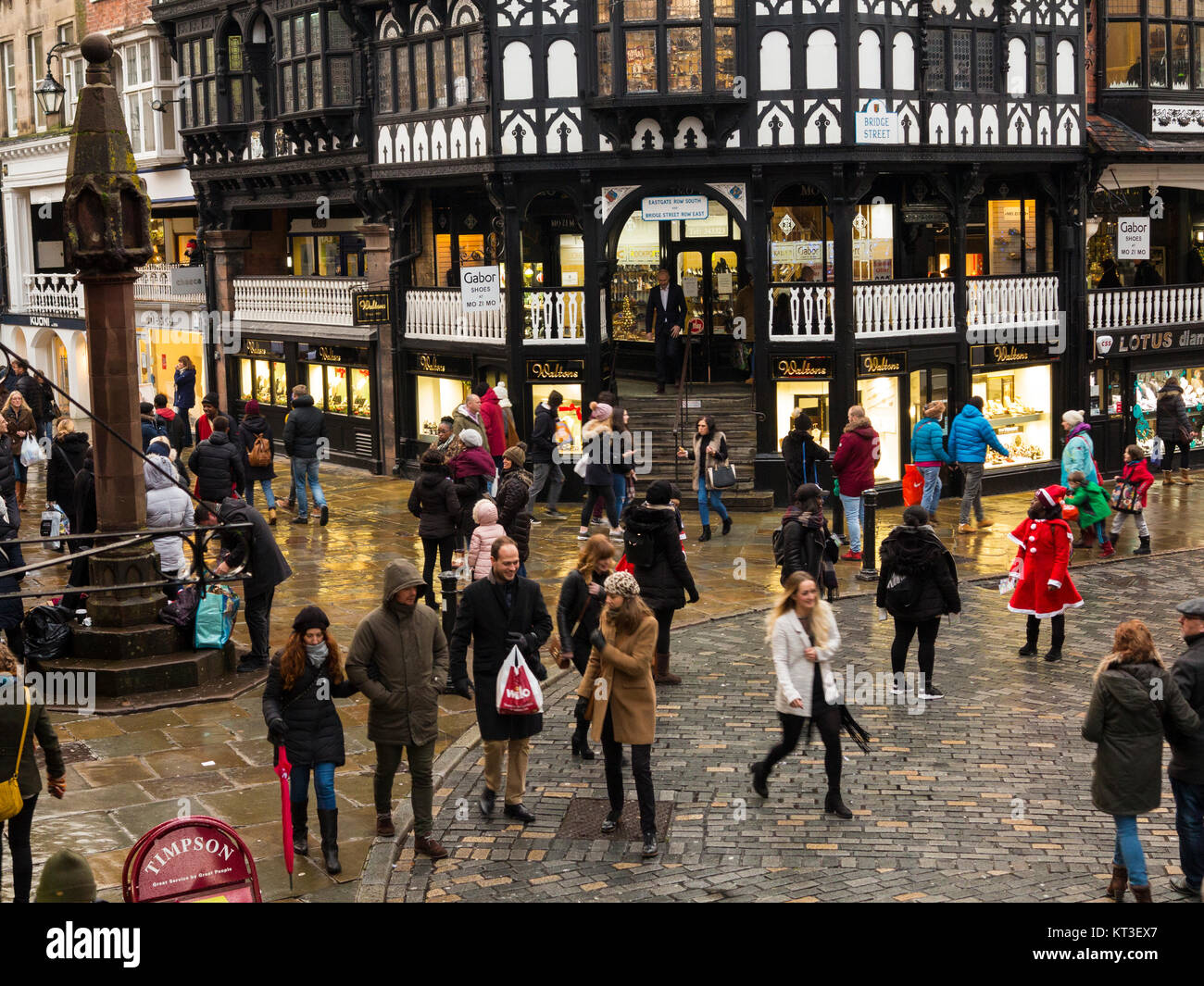 Christmas shoppers  walking over wet pavements and cobbles in the Roman town of Chester England around the medieval - Stock Image
