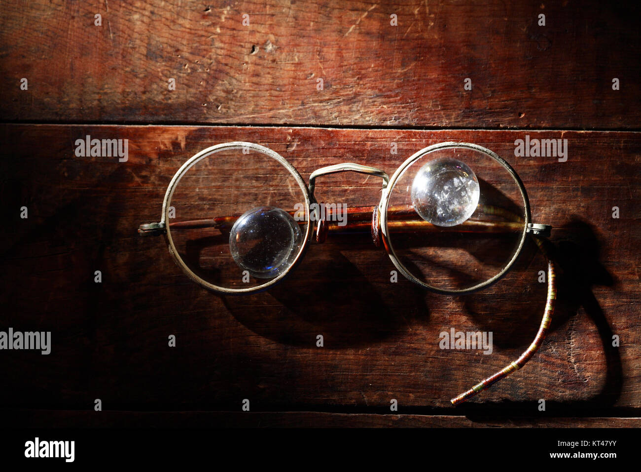 Old stylish spectacles closeup on wooden background - Stock Image