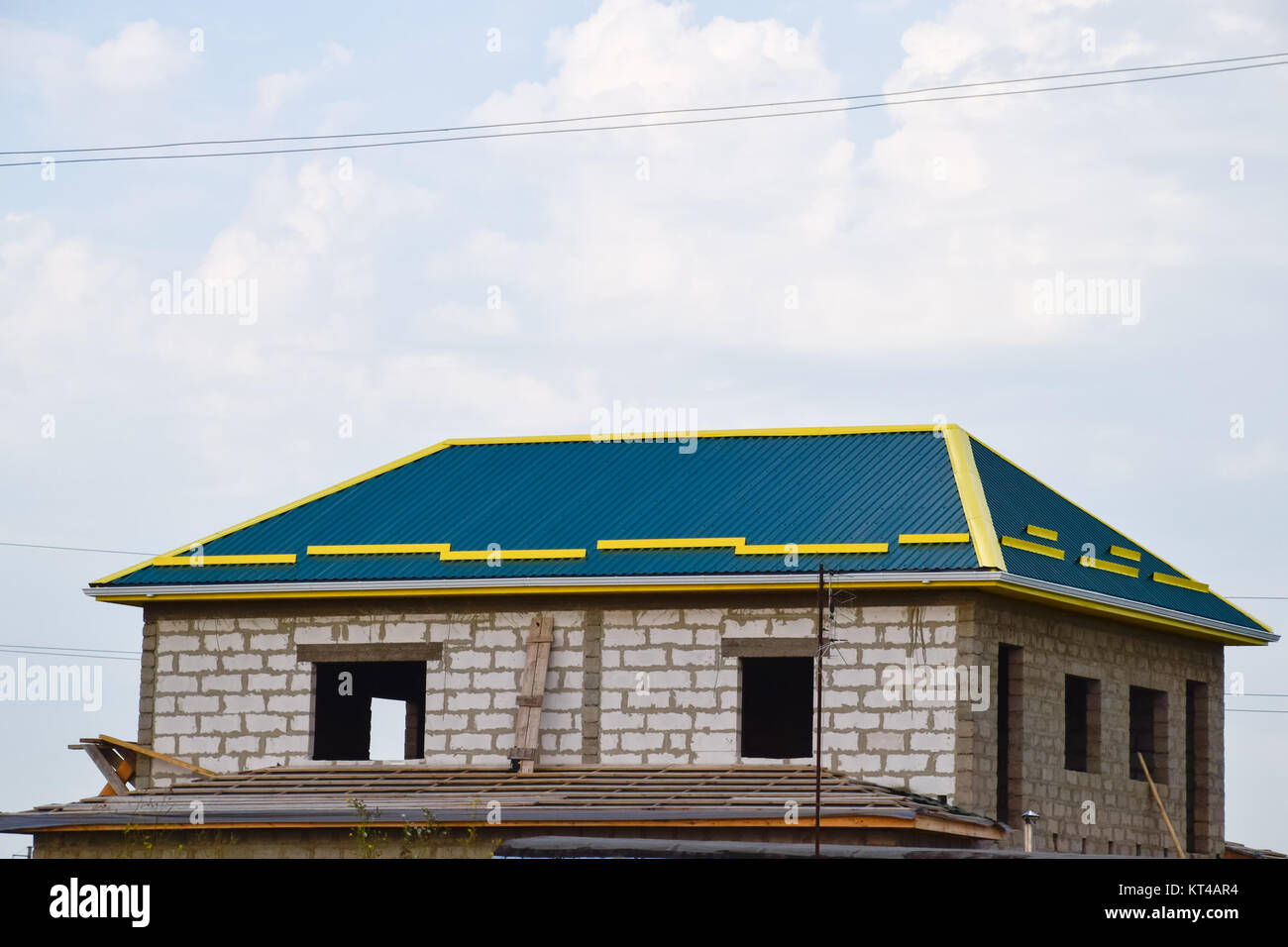A house with a roof made of metal sheets. Yellow skating on the roof - Stock Image