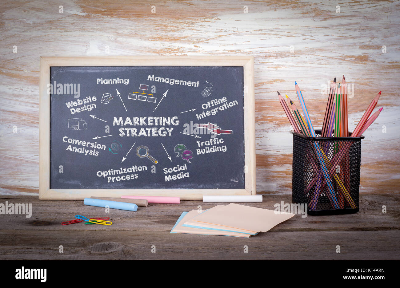marketing strategy concept. Chart with keywords and icons. Old wooden table with texture - Stock Image