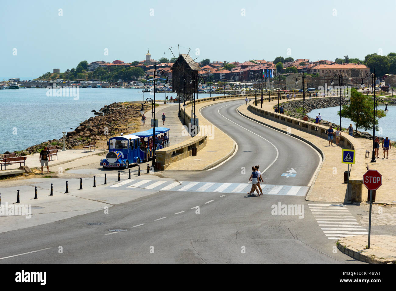 Coastal road and old wooden windmill on the ihtmus of the ancient town of Nesebar, Bulgaria - Stock Image