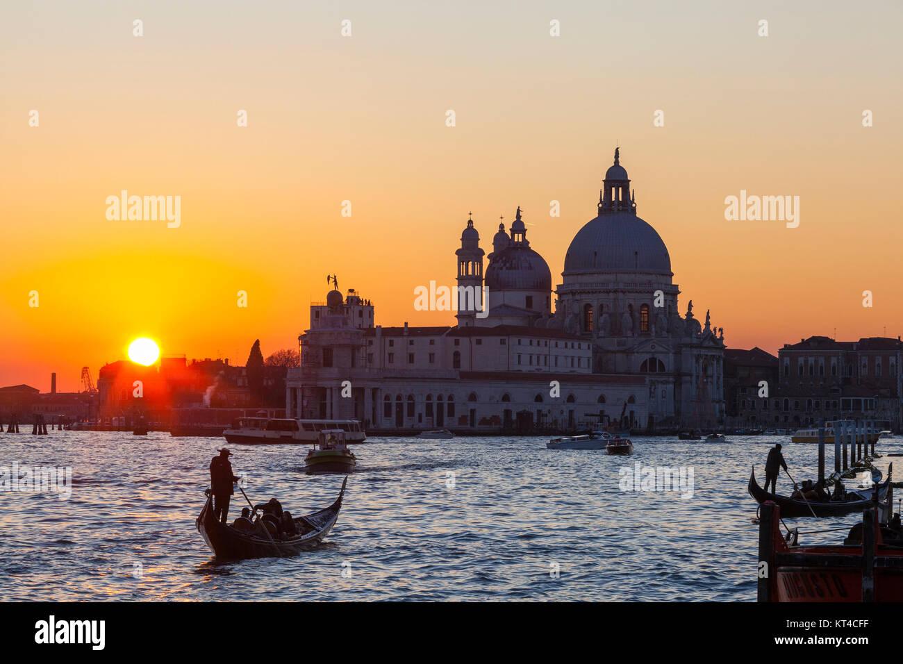 Colourful orange sunset over the Venice lagoon and Basilica di Santa Maria della Salute with  gondolas with tourists in ta romantic scene Stock Photo
