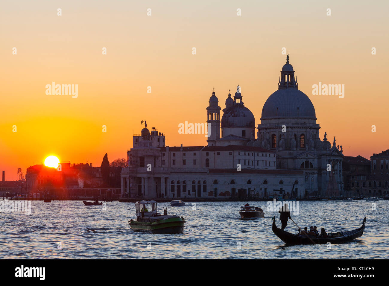 Colourful orange sunset over the Venice lagoon and Basilica di Santa Maria della Salute with boats and a gondola with tourists in the foreground Stock Photo