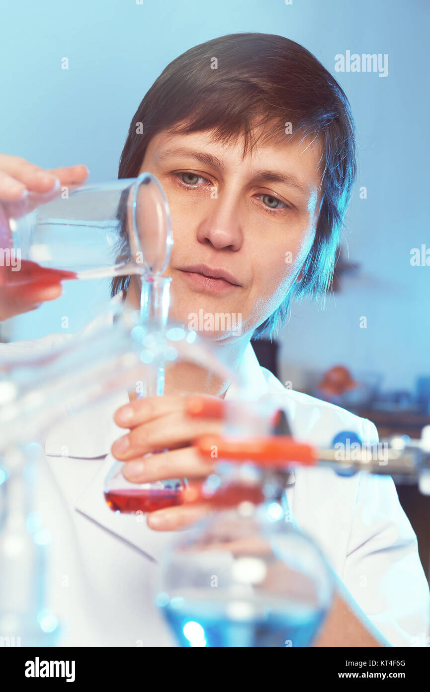 Portrait of a female scientist in white coat working in a chemical laboratory - Stock Image