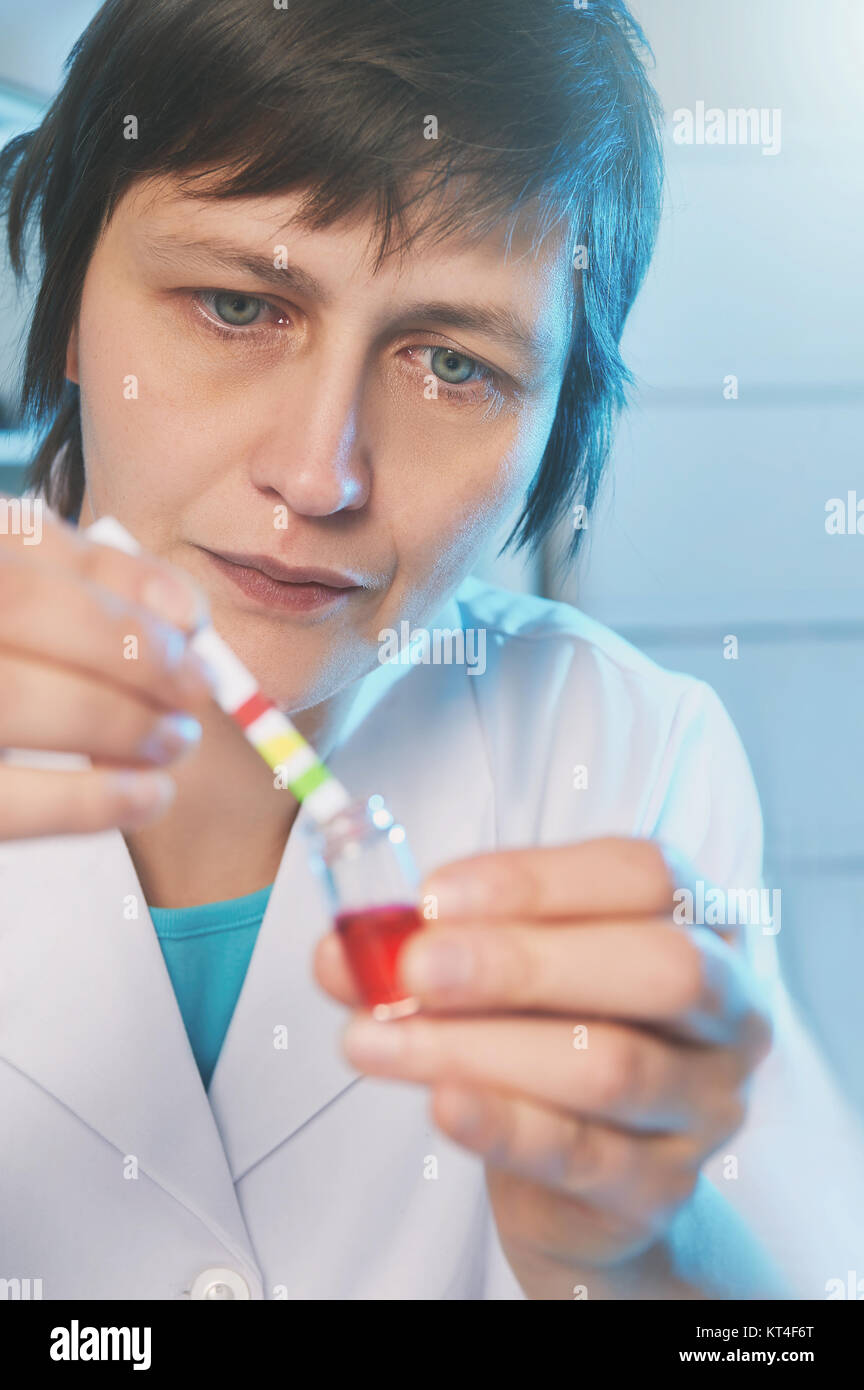 Portrait of a female scientist in white coat tests pH of a red liquid sample - Stock Image