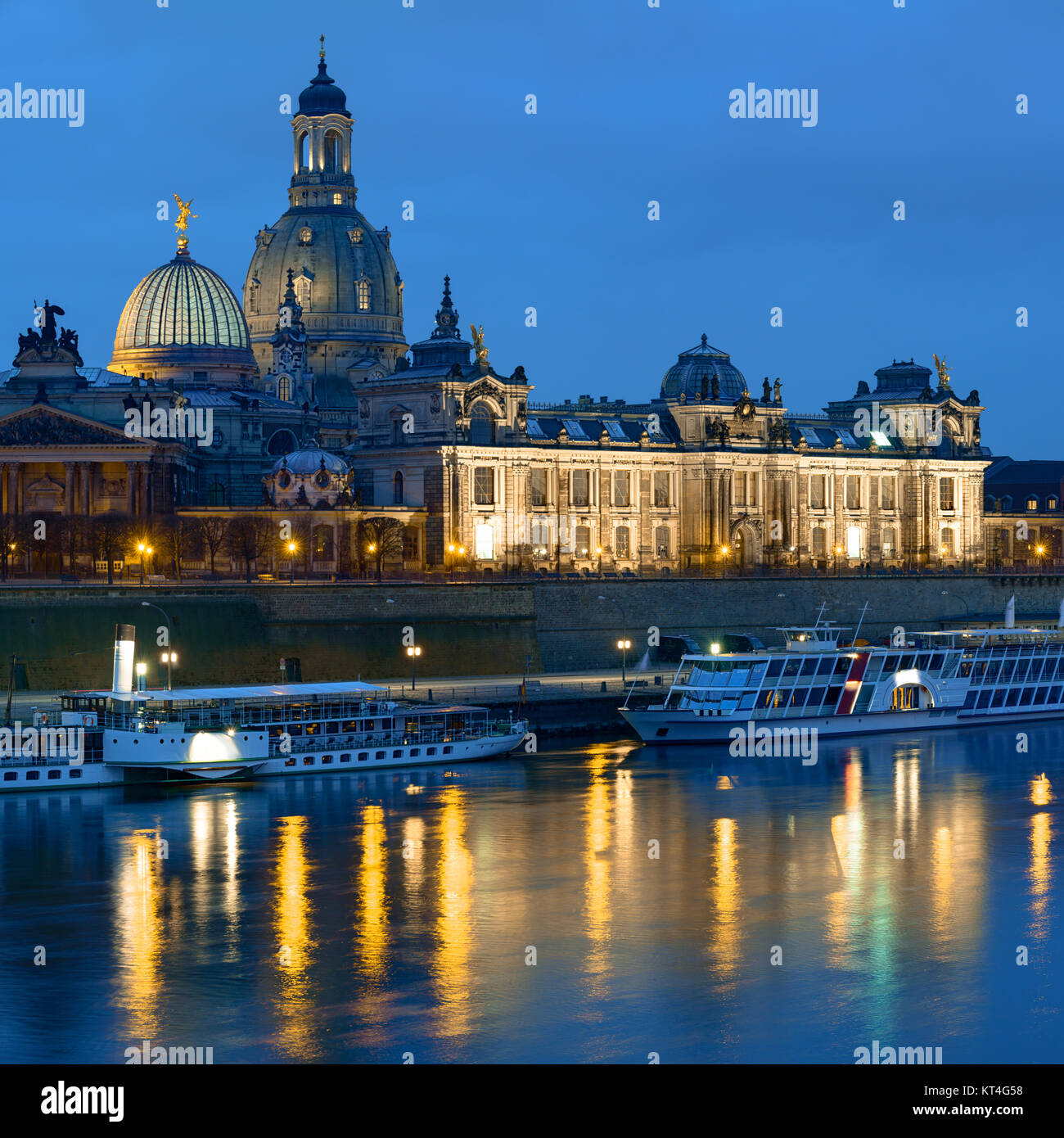 Dresden at night, with historical passenger ships, Bruhl's Terrace and Frauenkirchem reflected in the river - Stock Image