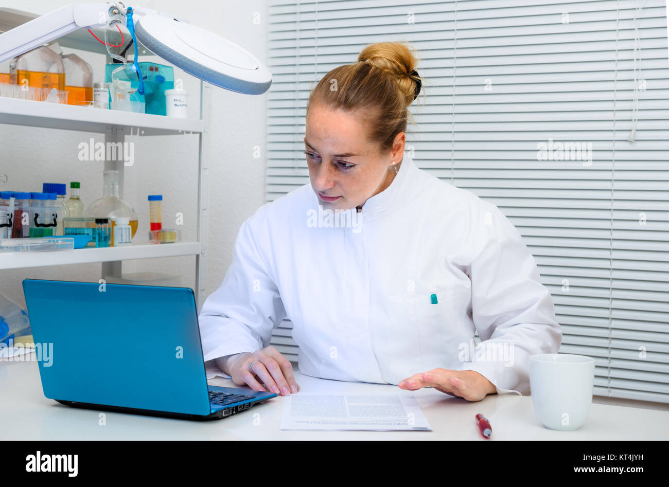 Experienced scientist works with portable computer in research laboratory - Stock Image