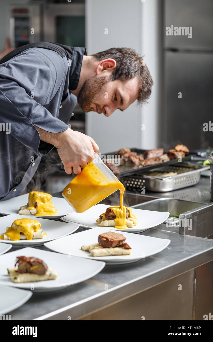 Chef pours sauce Stock Photo