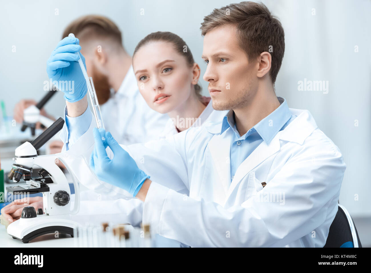 Young man and woman chemists looking at test tube in laboratory - Stock Image