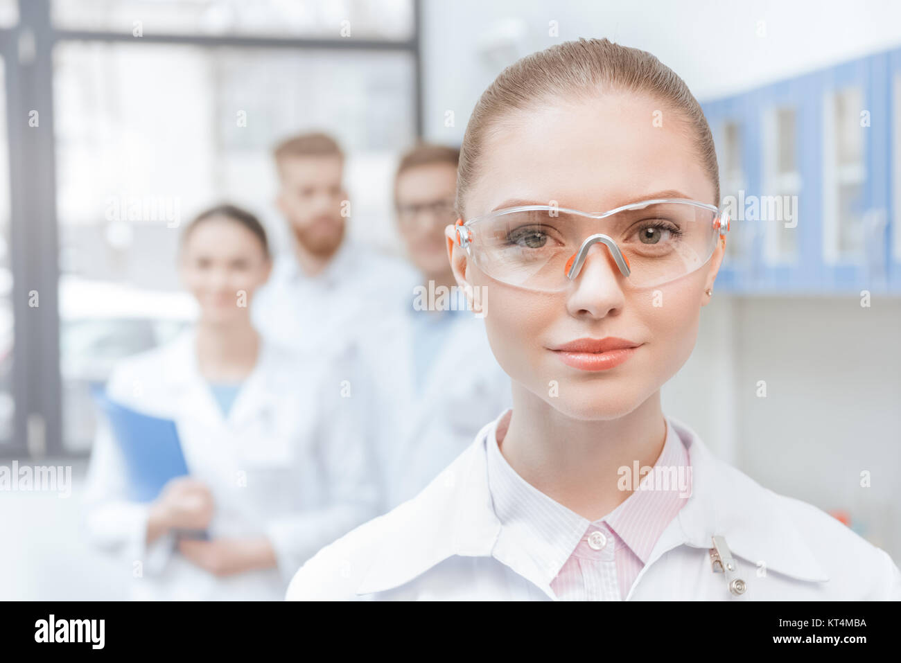 Close-up portrait of young woman scientist in lab coat and protective goggles smiling - Stock Image