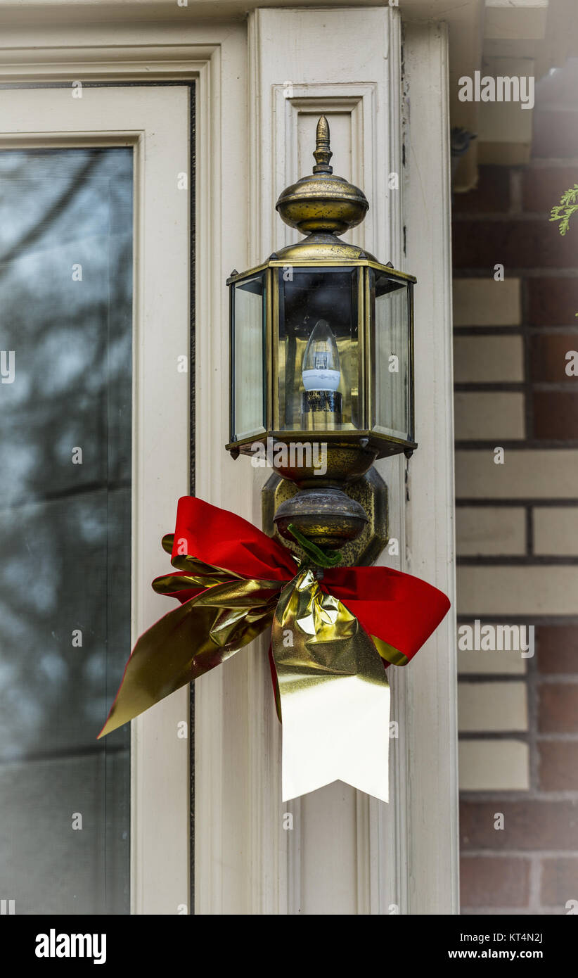 A lantern in doorway decorated for Christmas. - Stock Image