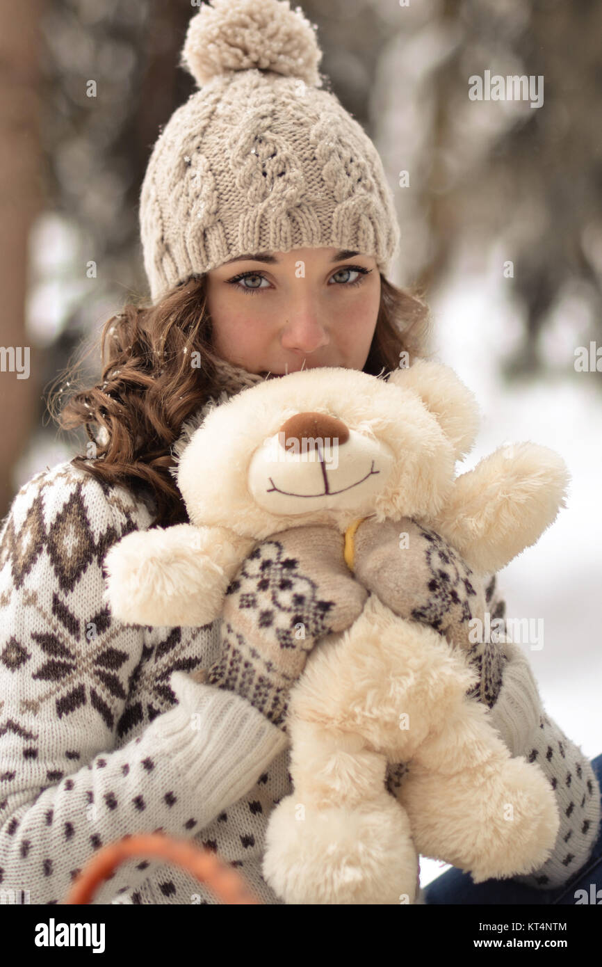 Beautiful, nice, smiling,little and wearing sweater hut and mittens and little girl with a teddy bear in winter Stock Photo
