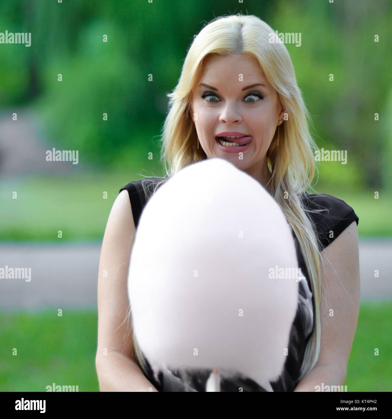 Crazy girl beautiful girl with open mouth,big crazy eyes and protruding tongue look at big cotton candy.Blonde want - Stock Image