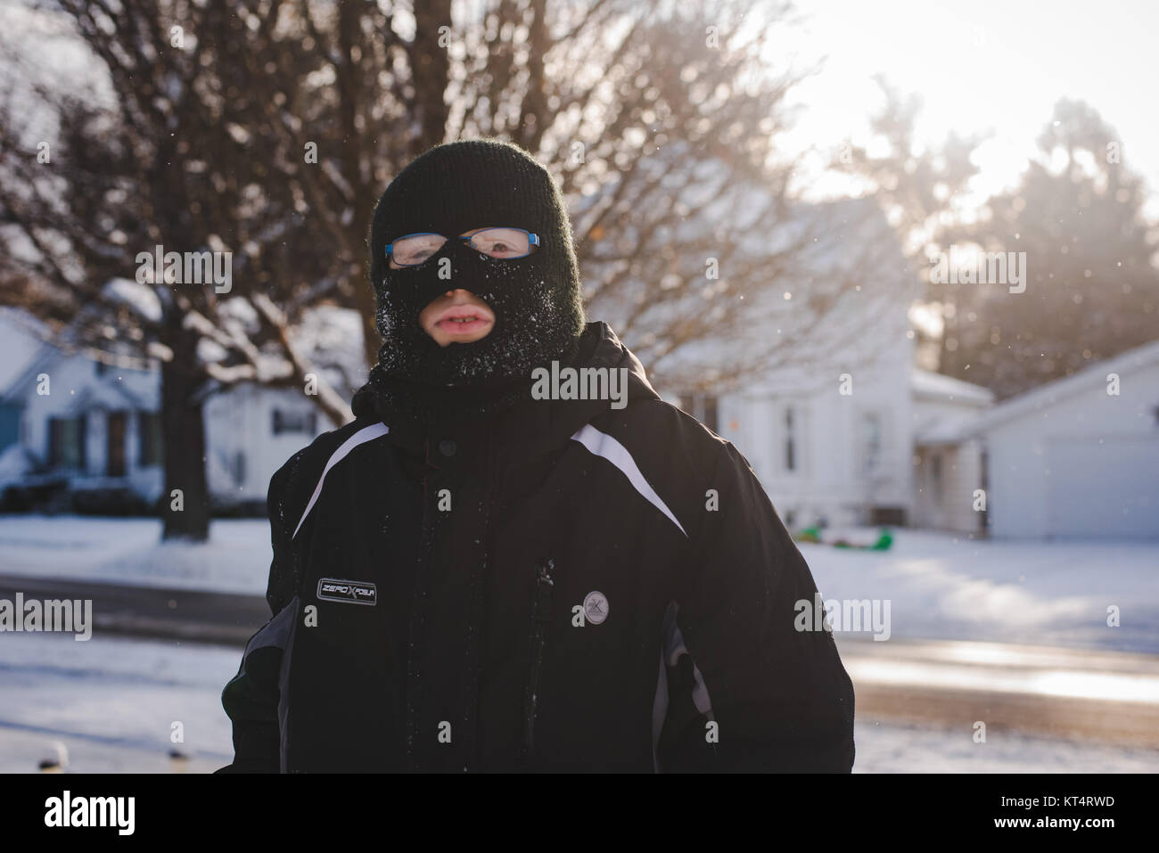 A young boy wearing a winter ski mask plays in the snow during the day. - Stock Image