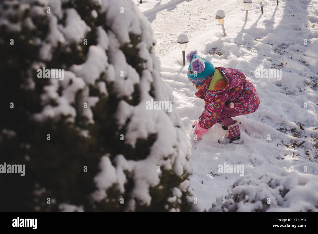 A toddler girl wearing a colorful coat plays in the snow. - Stock Image