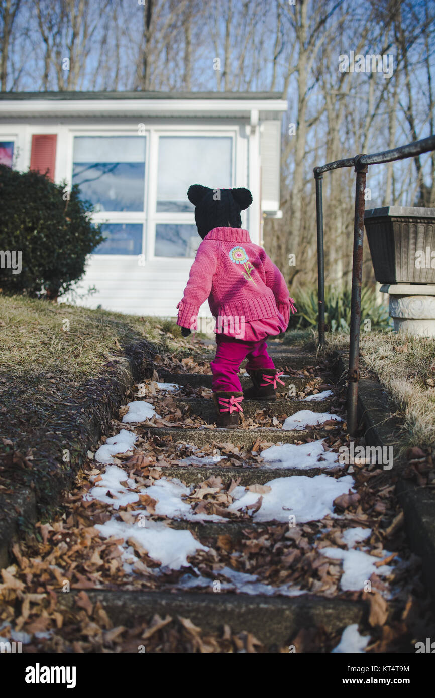 A child climbs up a flight of stone stairs wearing a sweater during the winter - Stock Image