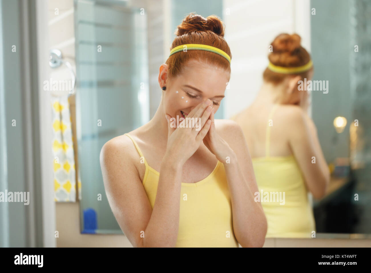 Redhead girl applying beauty cream in home bathroom at morning. Young woman taking care of her skin, looking and Stock Photo