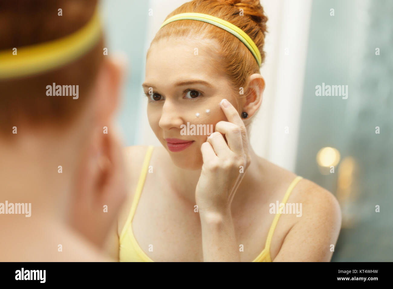 Redhead girl applying beauty cream in home bathroom at morning. Young woman taking care of her skin, looking at - Stock Image