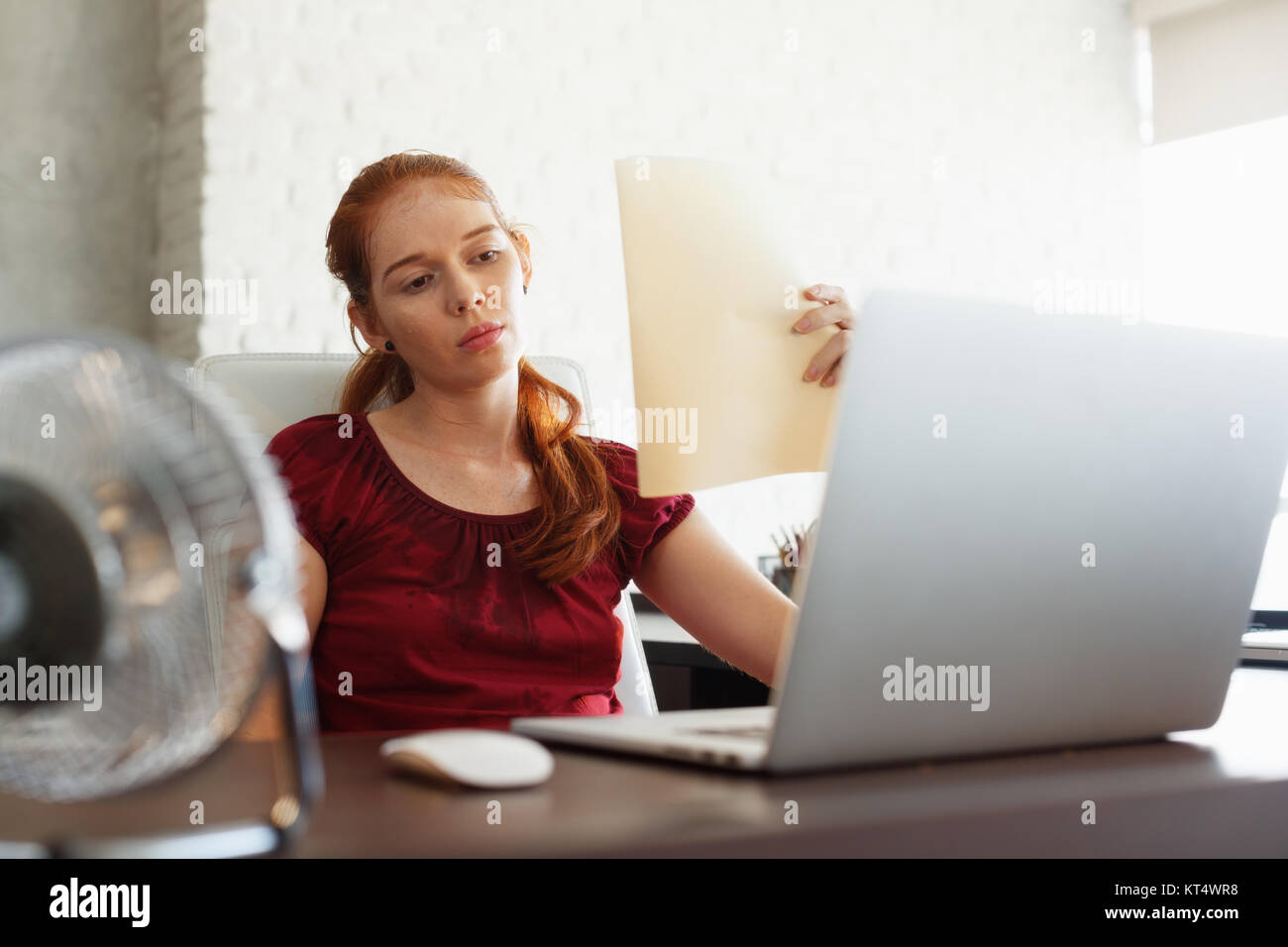 Portrait of young redhead woman working with computer laptop in office at summer during heatwave. The temperature - Stock Image