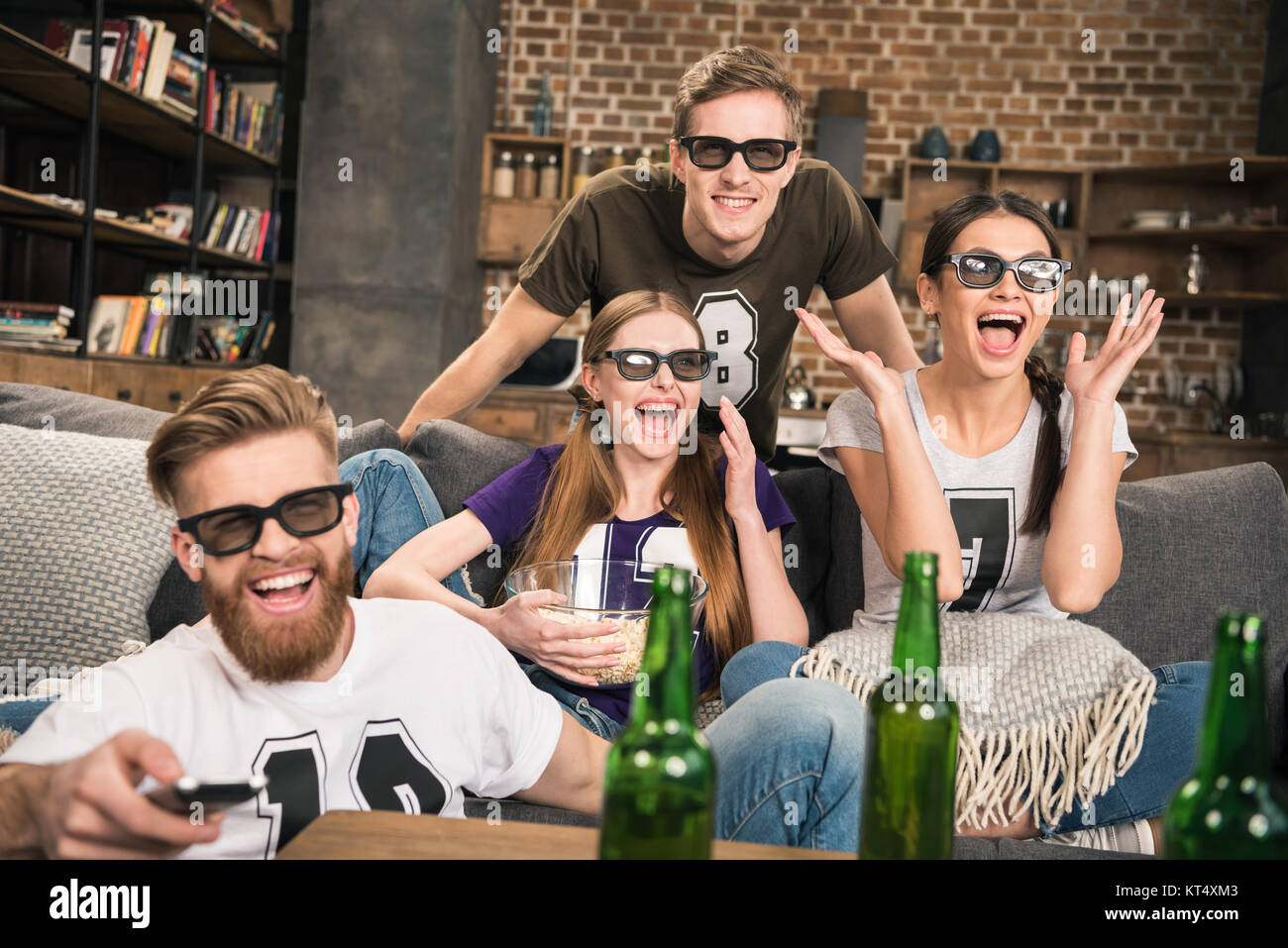 excited young friends in 3D glasses watching movie on sofa at home - Stock Image