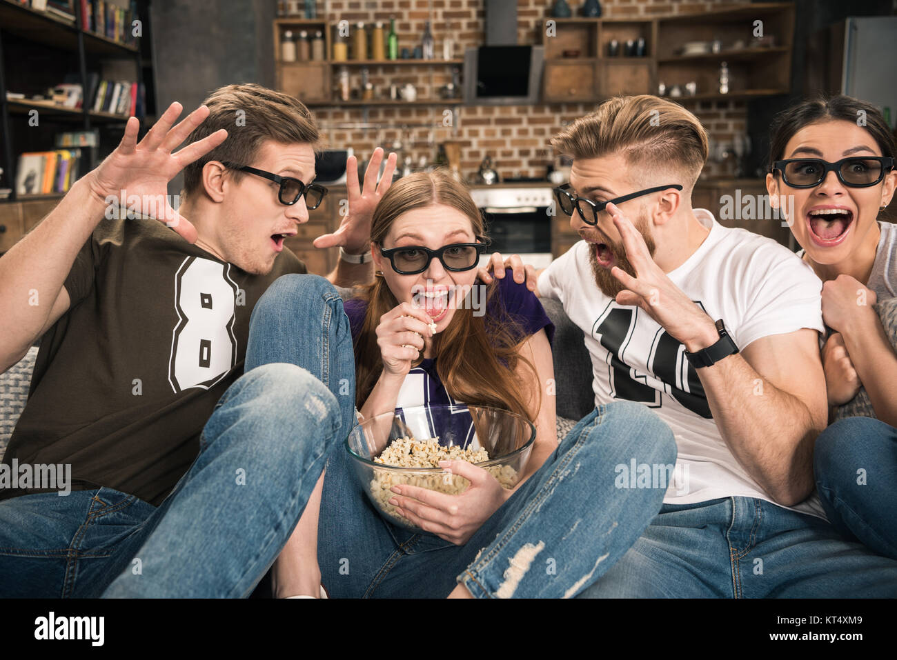 excited friends in 3D glasses watching movie at home - Stock Image