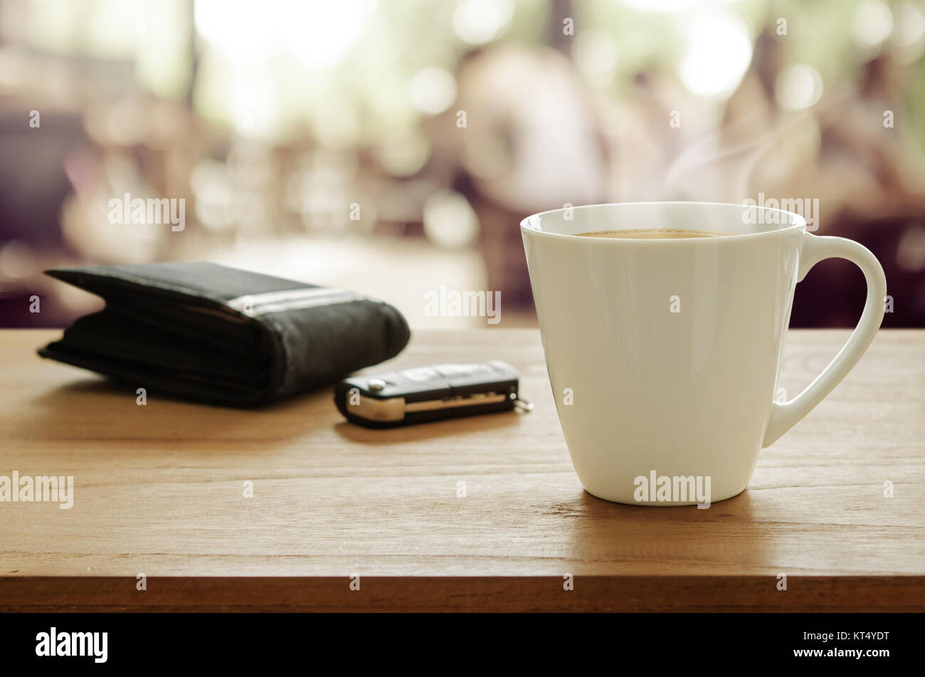 Cup of coffee, wallet and car remote key on wooden table in