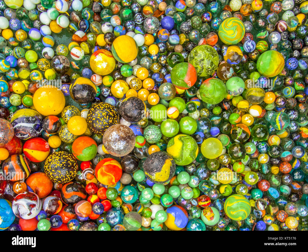 Glass marbles of different sizes in a color pattern - Stock Image