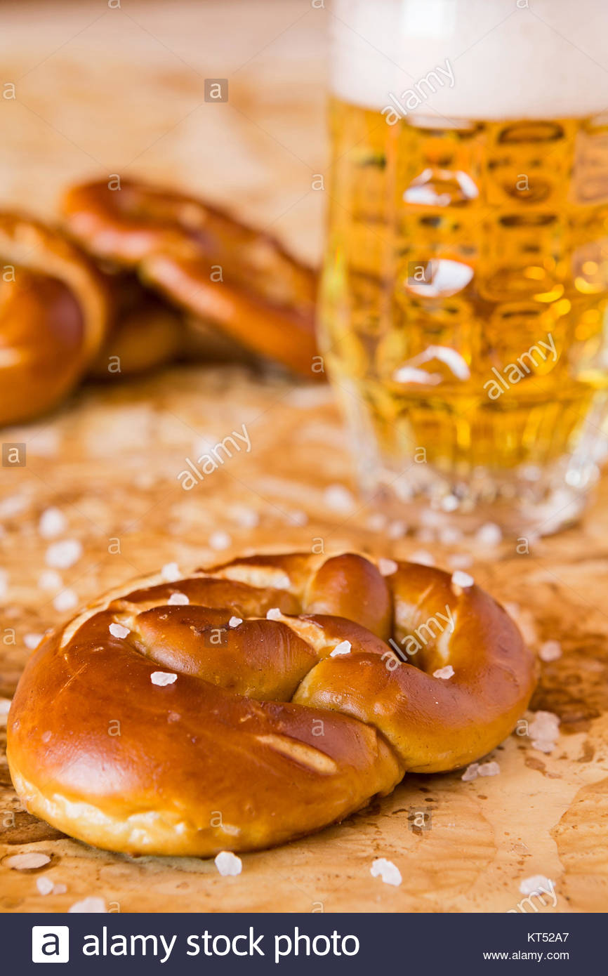Closeup of salty cooked pretzel and lager beer - Stock Image