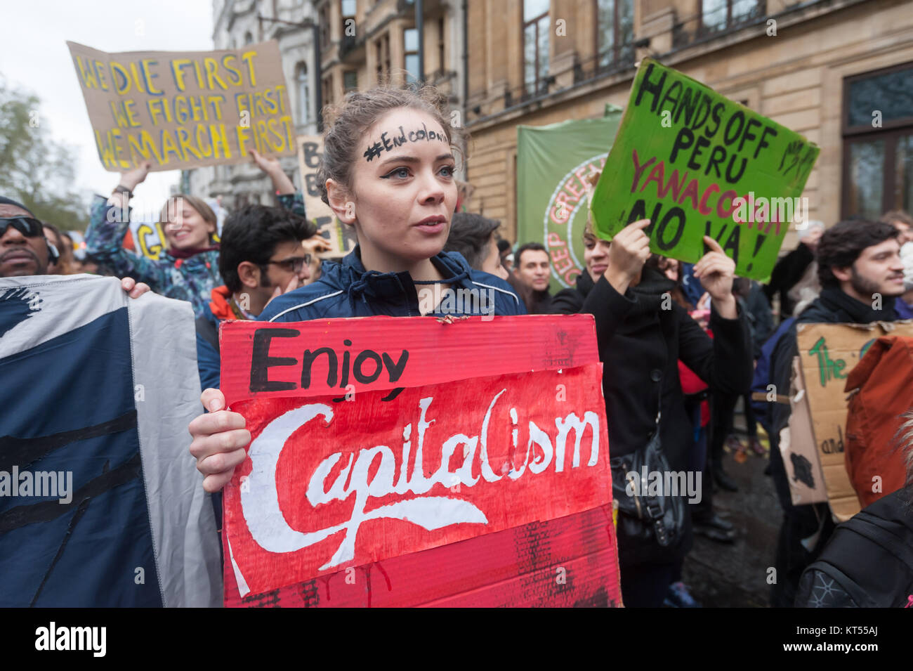 A woman with the hashtag #Endcolonialism across her forehead carries a poster 'Enjoy Capitalism - It Kills' - Stock Image
