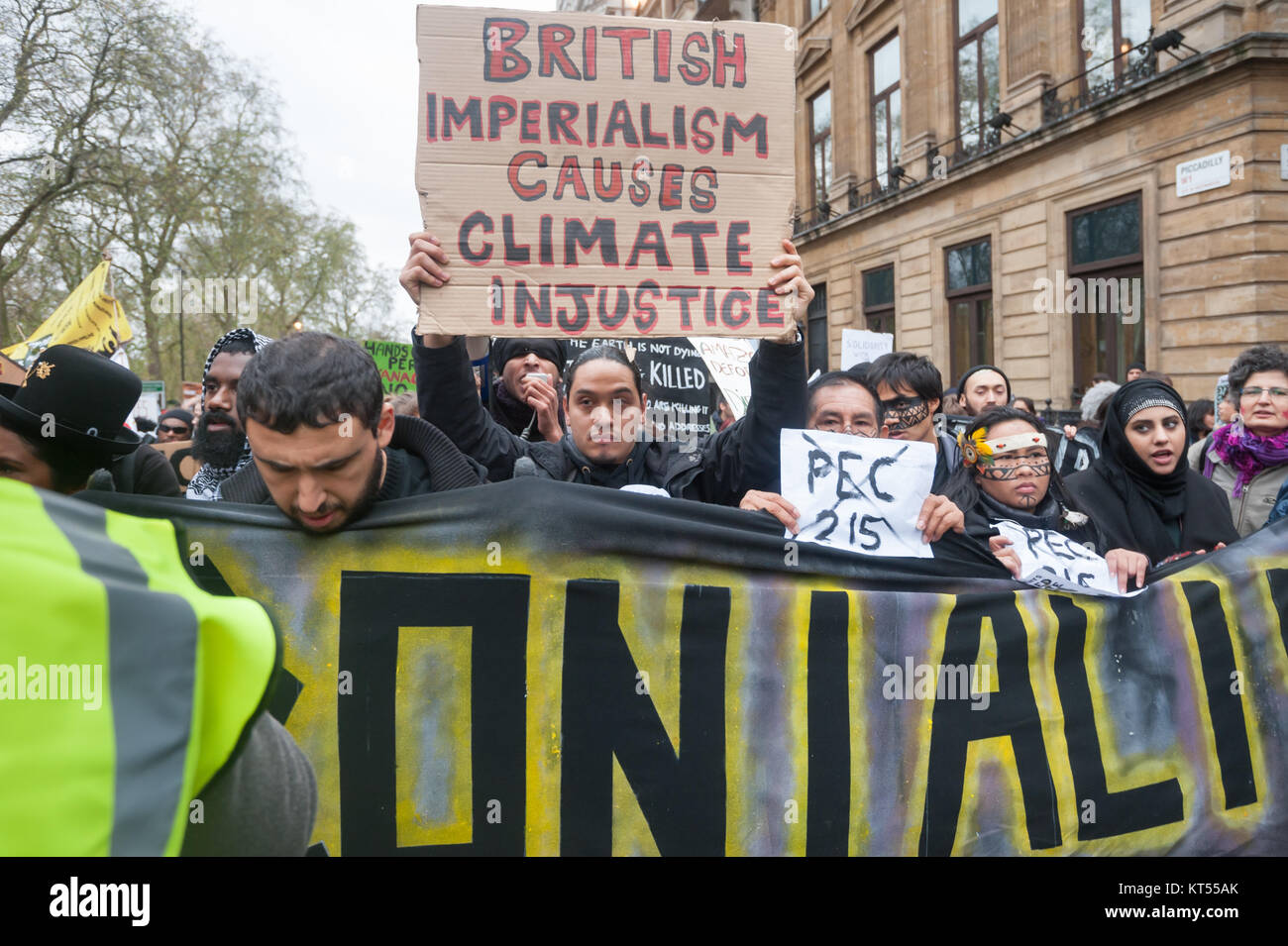 'British Imperialism Causes Climate Injustice poster behind people carrying the main banner in the in the Global - Stock Image