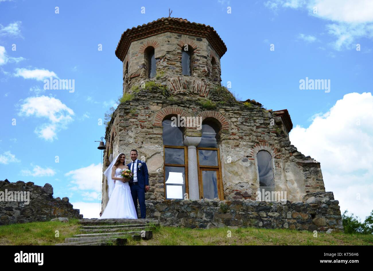 newlyweds next to the old church - Stock Image
