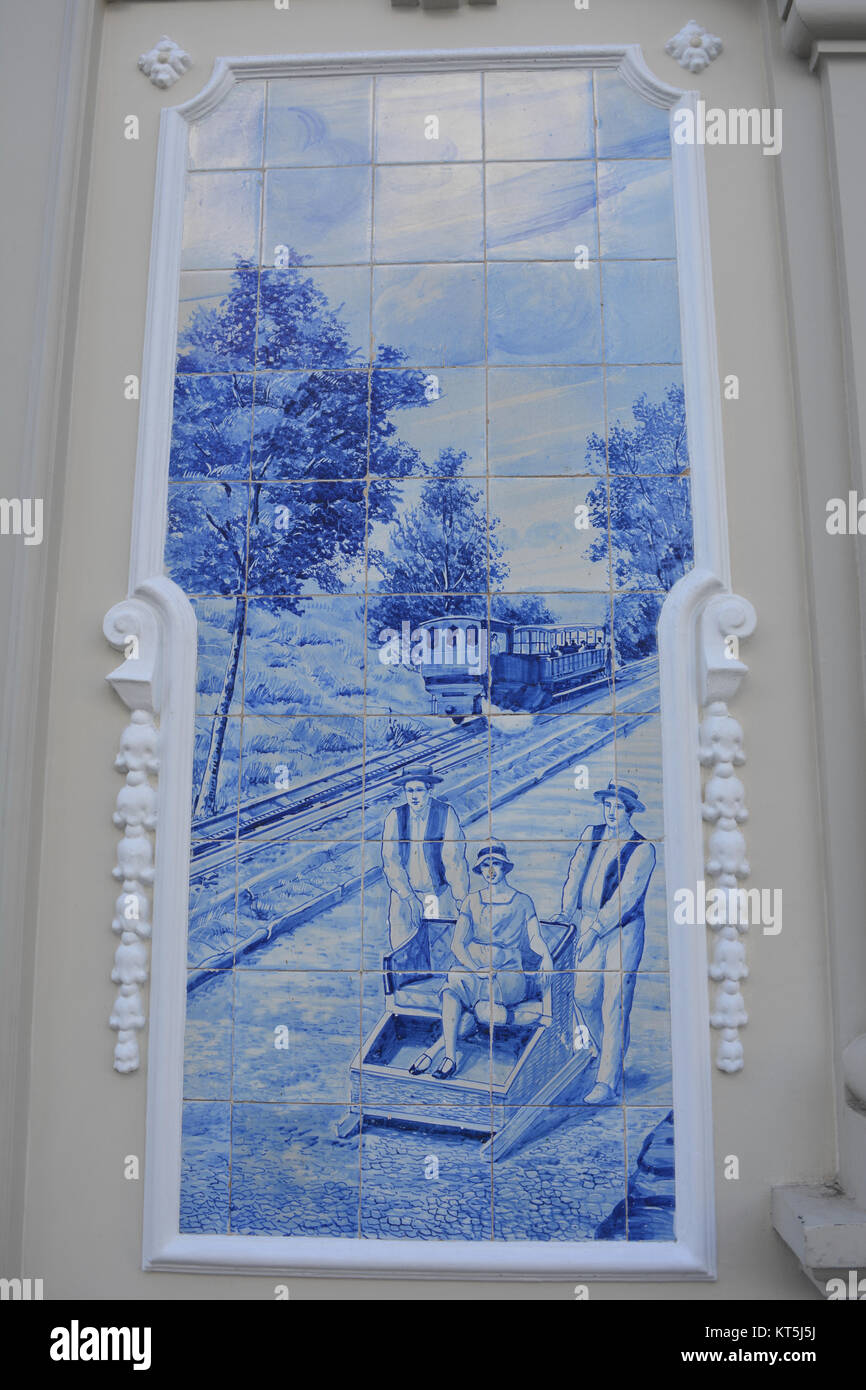 The famous wicker toboggan sled ride illustrated on hand painted blue tiles, or azulejos, on the facade of the Ritz - Stock Image